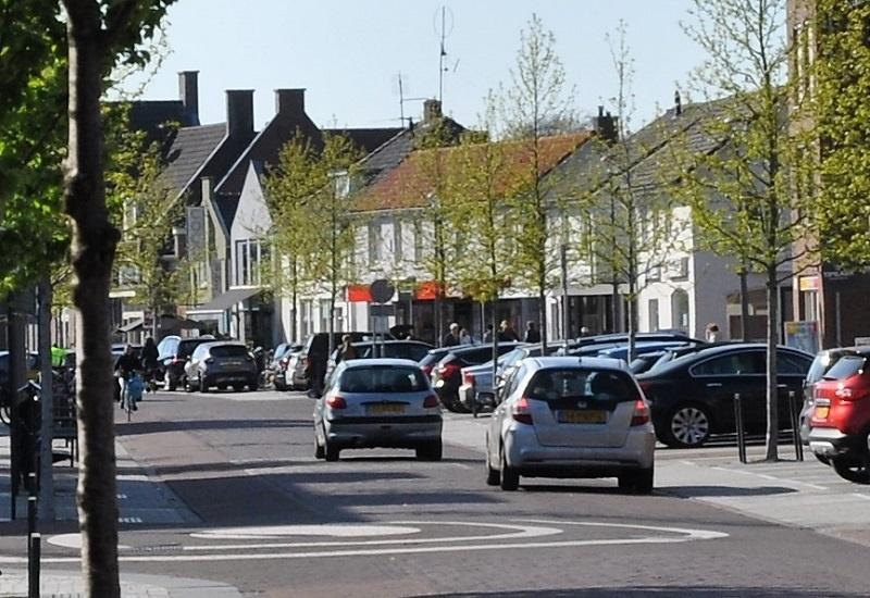 leefomgeving verkeer en vervoer, auto's, voetgangers en fietsers in winkelstraat met parkeerstroken